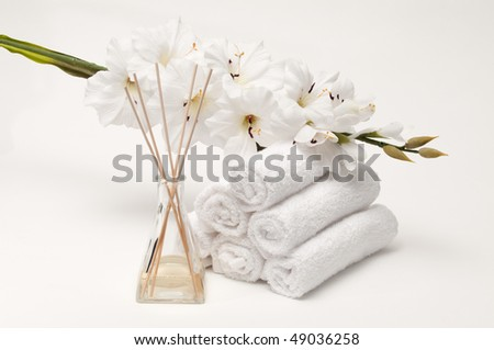 Aromatherapy spa diffuser with towels and flower on white - stock photo