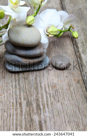 Aromatherapy spa set. Spa stones and orchid on wooden background - stock photo