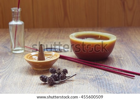 Aromatherapy still life with candle, bottle, aroma stick and incense cone in a ceramic stand on a wooden table.