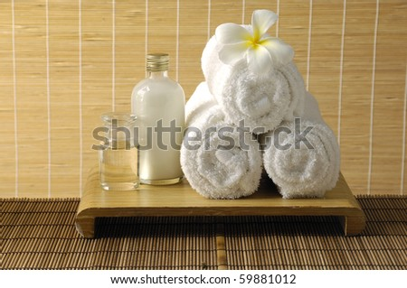Aromatherapy still life with frangipani on towels and oil on woven background