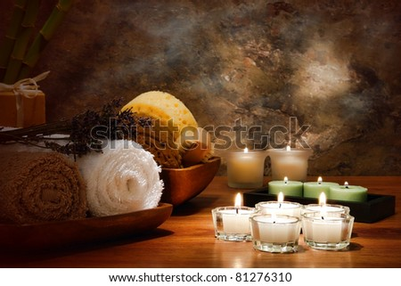 Aromatherapy votive candles burning with a soft glowing flame with towels and wellness treatment accessories in a spa - stock photo