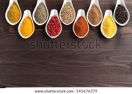 Aromatic and colorful spices in ceramic containers on a wooden background. Spice in the kitchen.