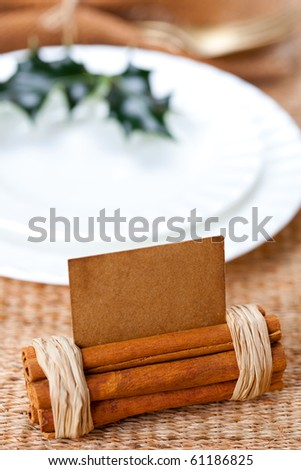 aromatic christmas place setting place  with card, holly twig in white plate, shallow dof - stock photo