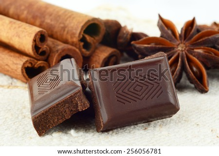 Aromatic close up set of chocolate,anise and cinnamon on white fibre material like flax - stock photo