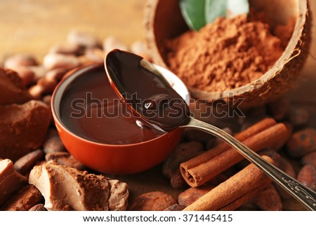 Aromatic cocoa harvest with tasty chocolate on wooden background, close up - stock photo