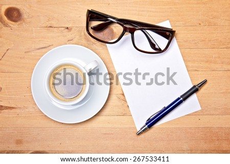 aromatic coffee on wood table with eyeglasses notepad and pen - stock photo