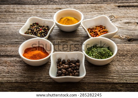 aromatic colorful spices in bowls on wooden background - stock photo