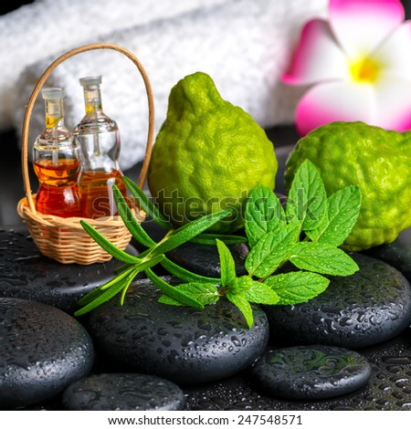 Aromatic concept of bergamot fruits, fresh mint, rosemary, candles, towels, flower and bottles essential oil on zen stones  - stock photo