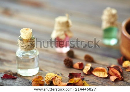 Aromatic essences in small bottles and dry leaves near by - stock photo