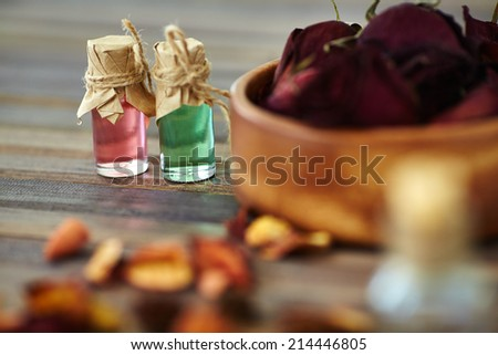 Aromatic essences in small bottles with dry roses near by - stock photo