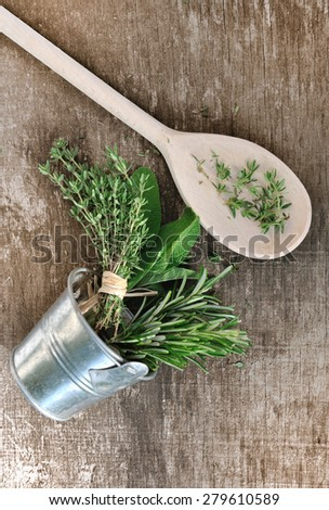 aromatic herbs in metal pot and wooden spoon on board - stock photo