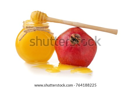 Aromatic honey in jar and pomegranate on white background