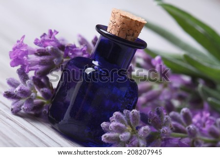 aromatic lavender oil in the blue bottle and beautiful flowers on the wooden table. Horizontal close-up   - stock photo