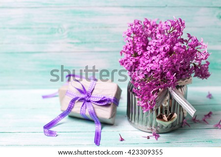 Aromatic  lilac flowers in vase and boxes with gifts on turquoise background. Selective focus. Place for text. - stock photo