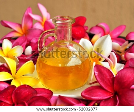 Aromatic massage oil and flowers - stock photo