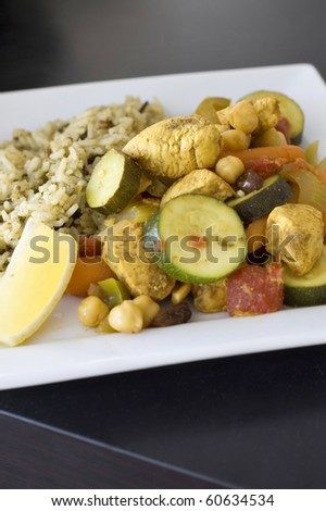 Aromatic Moroccan Chicken Stir Fry Plated with Whole Grain Rice Pilaf - stock photo