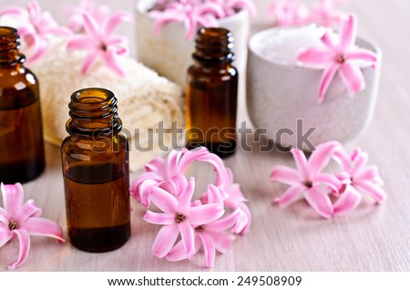 Aromatic oil for Spa in a glass vial surrounded by flowers pink hyacinth. - stock photo