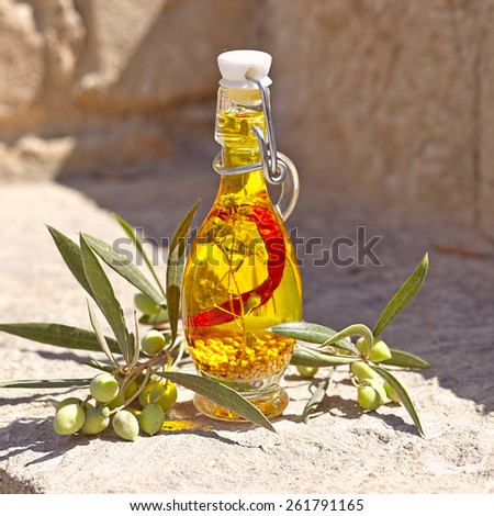 Aromatic olive oil in a bottle with herb, pepper and mustard seeds - stock photo