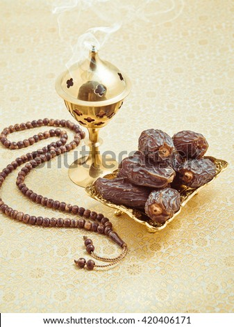 Aromatic oud burning in the burner, placed along with sweet arabian dates and islamic prayer beads. Muslim religious objects. - stock photo