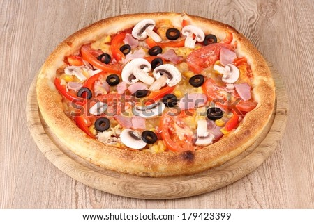 Aromatic pizza on wooden background - stock photo