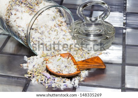 Aromatic potpourri with a mixture of natural flowers, plant shavings and spices spilling out of a glass jar onto a tiled surface with a small wooden scoop - stock photo
