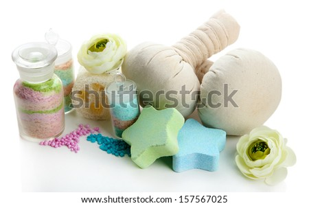 Aromatic salts in glass bottles and herbal compress balls for spa treatment, isolated on white