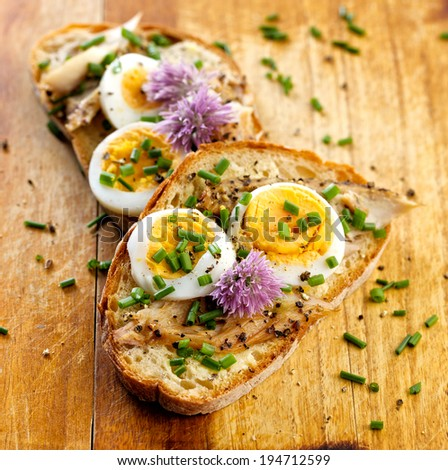 Aromatic sandwich with egg, mackerel and edible flowers of chives - stock photo