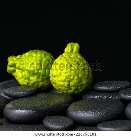 Aromatic spa concept of bergamot fruits on zen basalt black stones with dew, closeup  - stock photo