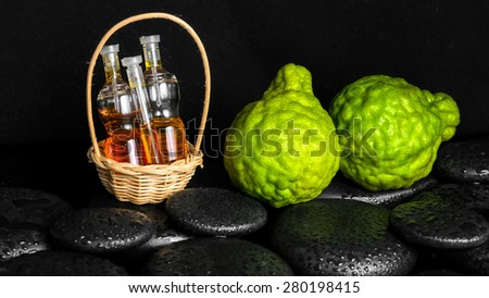 Aromatic spa concept of bottles essential oil in basket, bergamot and zen basalt stones with dew on black background, closeup  - stock photo