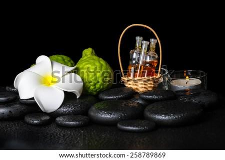Aromatic spa setting of bergamot fruits, candles, plumeria flower and bottles essential oil on zen stones - stock photo