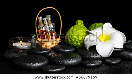 Aromatic spa setting of bergamot fruits, candles, plumeria flower and bottles essential oil on zen stones, closeup - stock photo