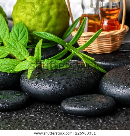 Aromatic spa still life of bottles essential oil, fresh mint, rosemary, bergamot fruits, towels and candles on zen stones, closeup   - stock photo