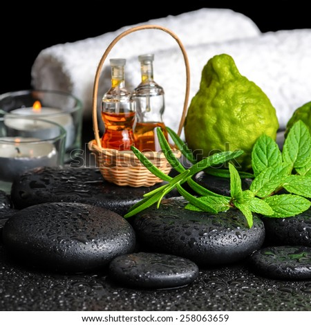 Aromatic spa still life of bottles essential oil, fresh mint, rosemary, bergamot fruits, towels and candles on zen stones , closeup - stock photo