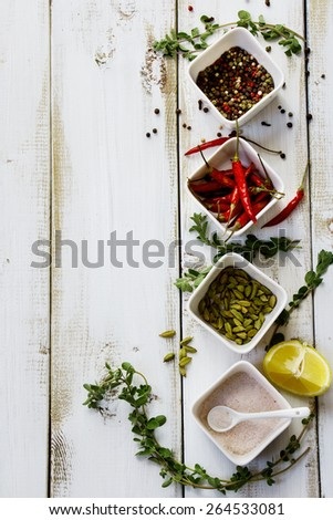 Aromatic spices and herbs over white wooden background. Food and cuisine ingredients with copyspace. - stock photo