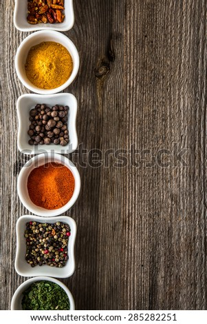 aromatic spices in bowls in horizontal row on wooden background - stock photo