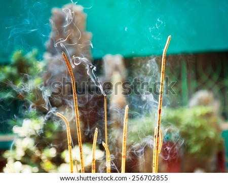 Aromatic sticks smolder in a Buddhist temple - stock photo