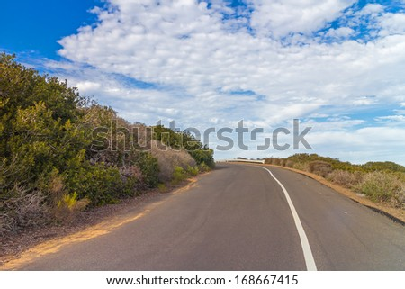 Around the bend on an ascending paved path. Empty, curving asphalt road going up. Bushes on both sides of the roadway. Blue sky and clouds background. Horizontal, perspective view. - stock photo