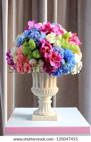Arrange flowers in a white roman vase - stock photo