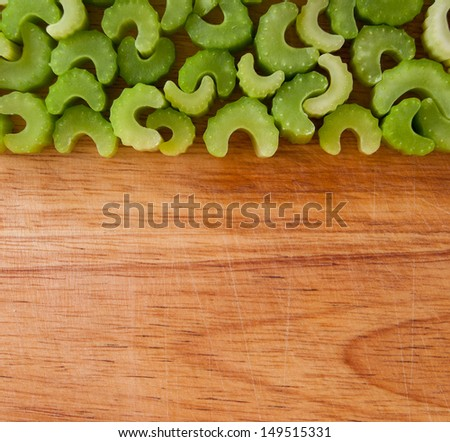 Arranged celery pieces against wooden chopping board background - stock photo