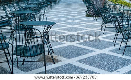 Arranged chairs and tables bistro bar outside on terrace  Empty restaurant terrace in summer without guests and people. Tourism area in Spain, perfect for gastronomy business, travel blog and magazine - stock photo