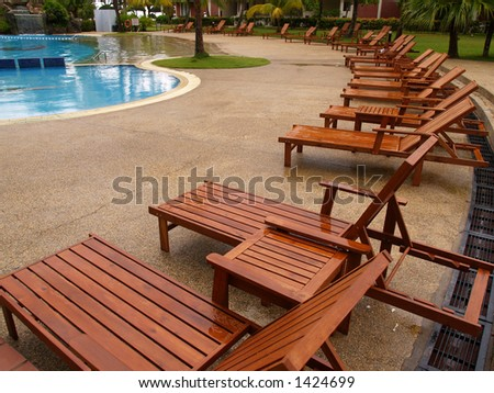 Arranged chairs next to swimming pool - stock photo