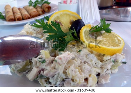 arranged delicious salad with olives, slice of lemon potatoes and mayonnaise