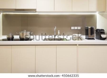 Arranged kitchen pot, plates and kitchen appliance on kitchen cabinet - stock photo