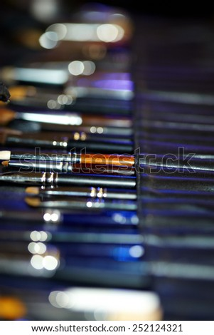 Arranged professional make-up brushes in leather case. Very shallow selective focus.  - stock photo