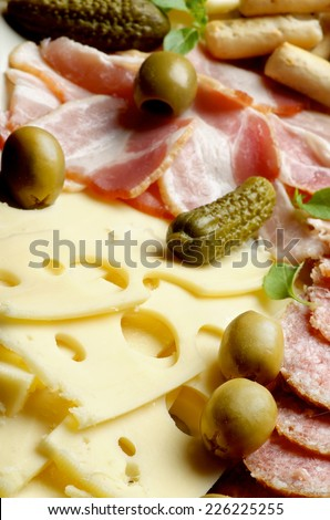Arrangement Delicious Emmental Cheese with Smoked Meat, Green Olives and Gherkins closeup. Focus on Foreground - stock photo