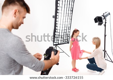 Arrangement finishing. Young male photographer fiddles with camera while little girl is getting ready to shooting - stock photo