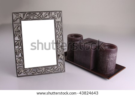 Arrangement of candles next to a blanked-out photo frame. - stock photo