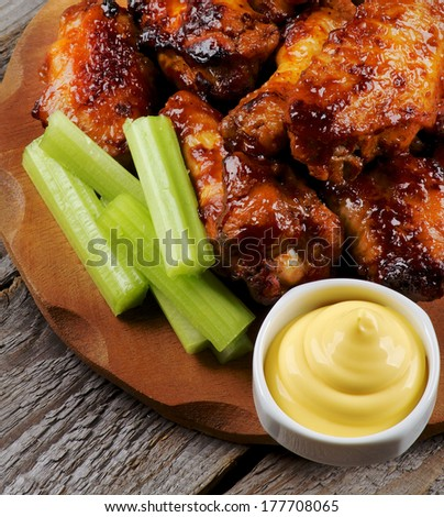 Arrangement of Celery Sticks, Cheese Sauce and Barbecue  Chicken Legs and Wings Barbecue closeup on Wooden Plate - stock photo