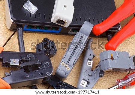 Arrangement of Computer Network Tools for Crimping, Cutting and Connecting with Router closeup on Wooden background