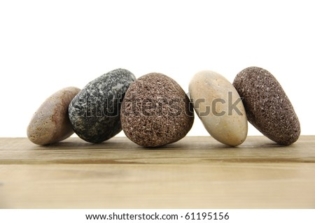 arrangement of different shape rocks on a wood board - stock photo